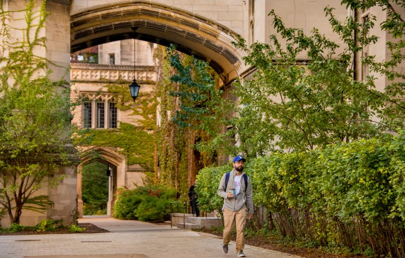 A student walks under an archway in the SSD Quad