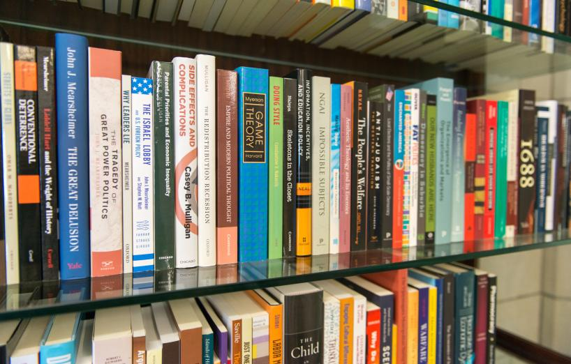 faculty books displayed on a bookshelf