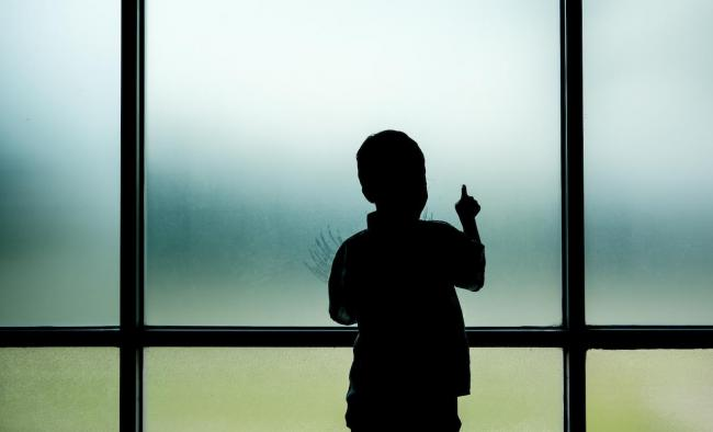 child alone standing at window